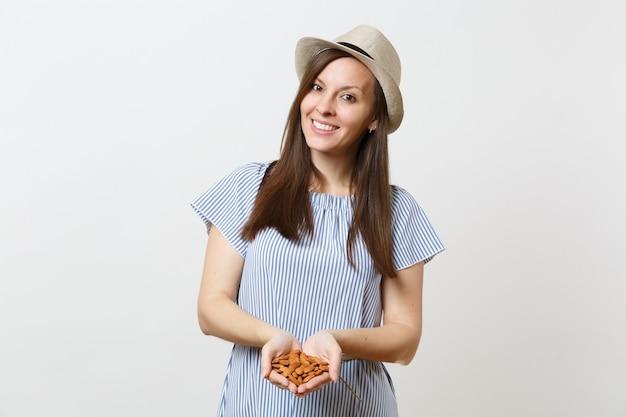 Ritratto di giovane donna sorridente tenere in mano mandorle non lavorate marroni noci isolate su sfondo bianco. una corretta alimentazione, cibo vegano mangiare vegetariano, concetto di dieta stile di vita sano. copia spazio