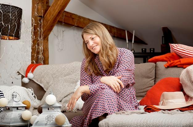 Ritratto di una giovane donna sorridente è seduto a casa su un divano tra le decorazioni natalizie