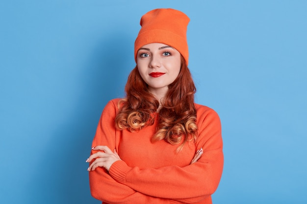 Ritratto di giovane donna sorridente in maglione arancione e berretto, in piedi con le braccia conserte