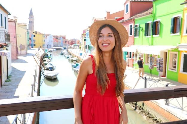 Ritratto di giovane donna sorridente in abito rosso e cappello sul ponte nel centro storico di burano, venezia, italia