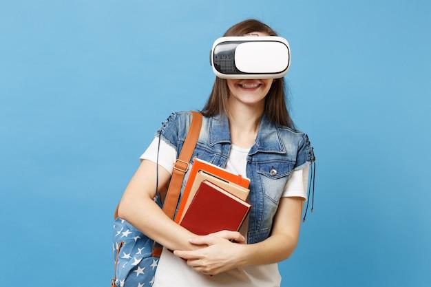 Ritratto di giovane studentessa sorridente in abiti in denim con zaino che indossa occhiali per realtà virtuale, in possesso di libri scolastici isolati su sfondo blu. istruzione al college universitario di scuola superiore.