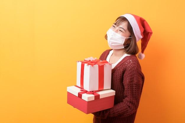 Ritratto di giovane donna sorridente nella mascherina chirurgica che porta il cappello rosso di babbo natale isolato