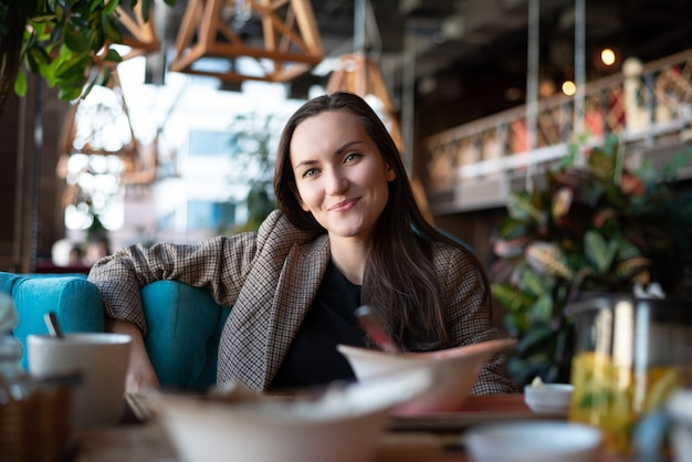 Ritratto di una giovane donna sorridente a un tavolo in un ristorante con uno sfocato
