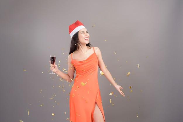 Un ritratto di giovane donna sorridente che indossa il cappello rosso di babbo natale è in possesso di un bicchiere di vino