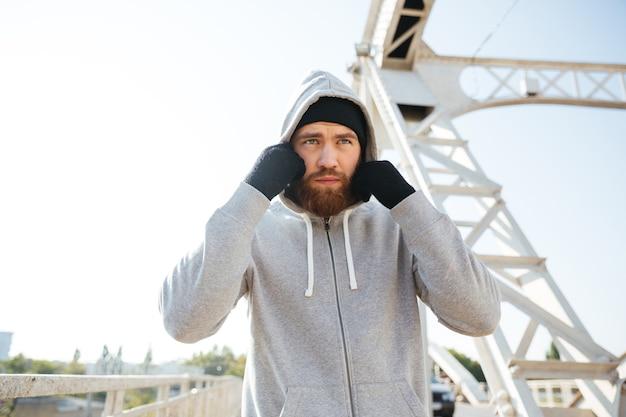 Ritratto di un giovane atleta sportivo in felpa con cappuccio in piedi sul ponte urbano