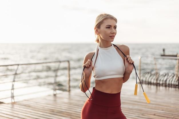 Ritratto di una giovane donna sportiva in abiti sportivi con una corda per saltare sportiva in posa sulla spiaggia all'alba