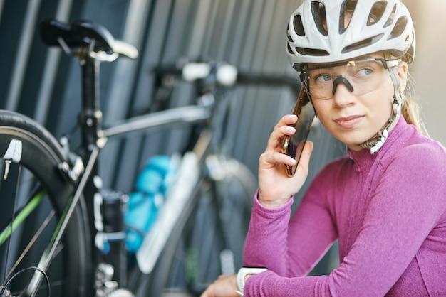 Ritratto di giovane ciclista donna sportiva caucasica che guarda da parte facendo una chiamata usando