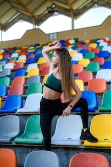 Ritratto di una giovane donna sportiva sulle scale dopo il jogging mattutino nello stadio della città. stile di vita sano in città
