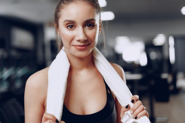 Ritratto di una giovane donna indoeuropea sportiva formazione in un fitness club