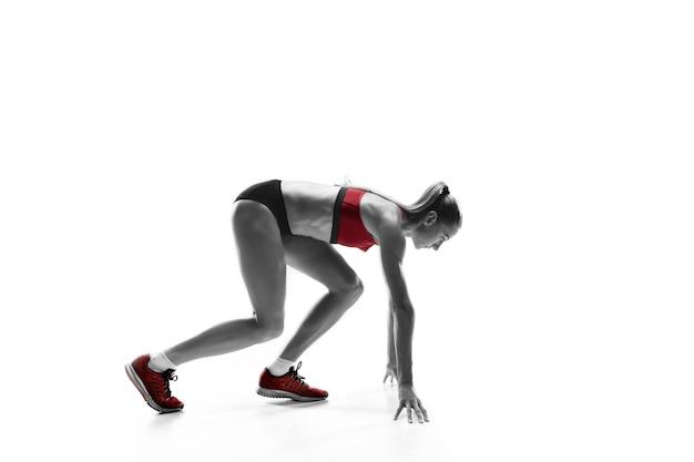 Ritratto di giovane donna sportiva al blocco di partenza della gara isolato su sfondo bianco studio. il velocista, il jogger, l'esercizio, l'allenamento, il fitness, l'allenamento, il concetto di jogging. profilo