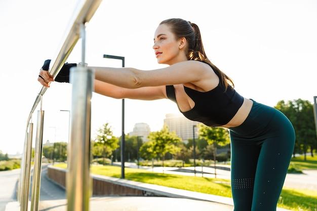 Ritratto di giovane donna sportiva che indossa tuta da ginnastica appoggiata alla ringhiera e allungando il suo corpo durante l'allenamento nel parco verde