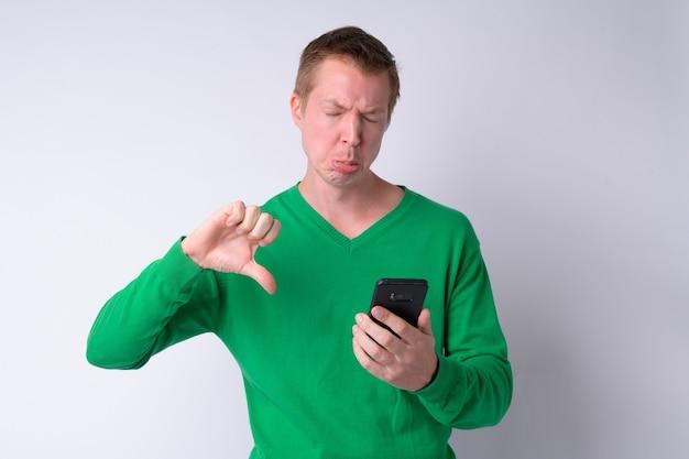 Ritratto di giovane uomo stressato utilizzando il telefono e ottenendo cattive notizie