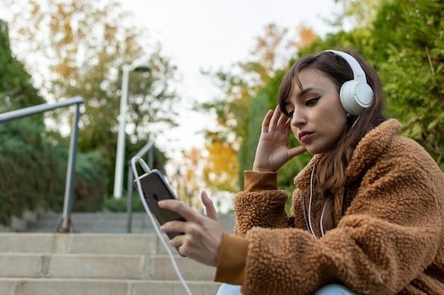 Ritratto di una ragazza giovane studente seduto sulle scale. ascoltando della musica.