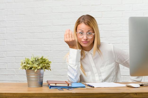 Ritratto di giovane studente seduto sulla sua scrivania facendo compiti facendo un tipico gesto italiano, sorridendo e guardando dritto, simbolo o espressione con la mano, molto naturale