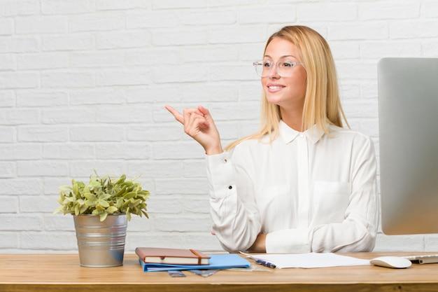 Ritratto di giovane studente seduto sulla sua scrivania facendo compiti che punta al lato