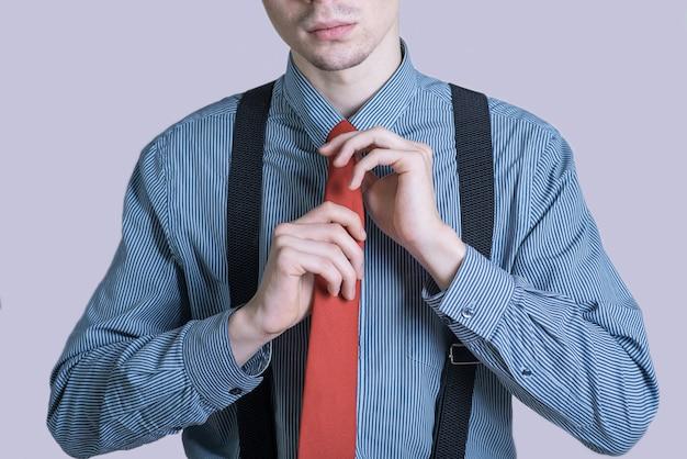 Ritratto di un ragazzo giovane ed elegante in un vestito che legando una cravatta