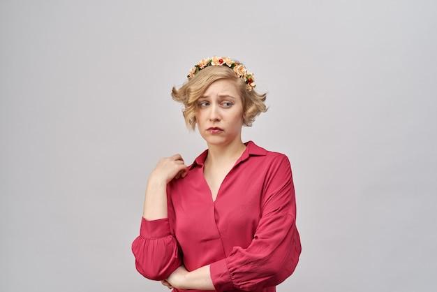Ritratto di giovane ragazza alla moda in abiti festivi con gli occhi tristi e confuso l'espressione annoiata sul suo viso. ha messo in dubbio lo sguardo di lato e vicino alla depressione.