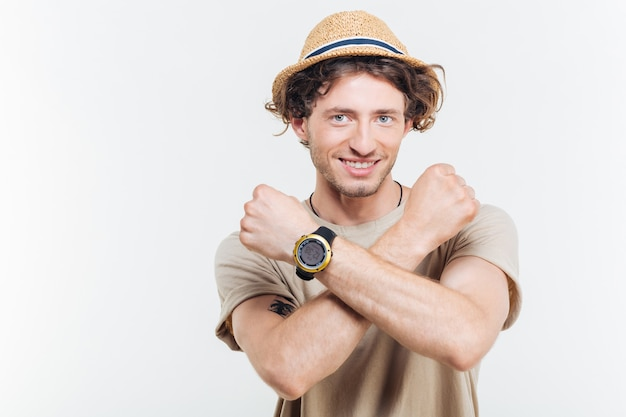 Ritratto di un giovane uomo elegante che mostra il gesto di arresto con le braccia incrociate isolato su uno sfondo bianco