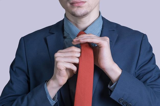 Ritratto di un uomo giovane ed elegante in un vestito che sta legando una cravatta