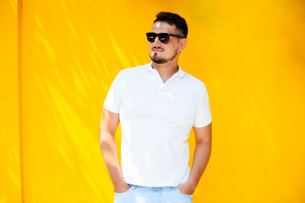 Ritratto di un giovane uomo alla moda con la barba in occhiali da sole e una maglietta bianca
