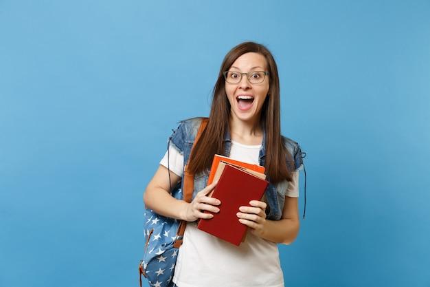 Ritratto di giovane studentessa felice stupita sorpresa in vetri con la bocca aperta con lo zaino che tiene i libri di scuola isolati su fondo blu. istruzione nel concetto di college universitario di liceo.