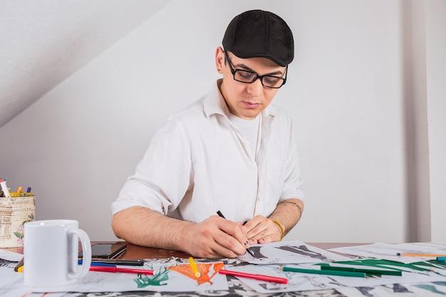 Ritratto di un giovane sarto che disegna nel suo laboratorio.