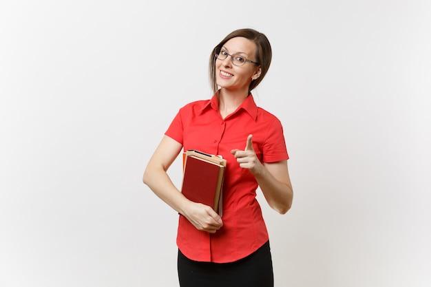 Ritratto di giovane insegnante donna in camicia rossa, gonna nera e occhiali che tengono libri, puntando la fotocamera del dito indice isolata su sfondo bianco. istruzione o insegnamento nel concetto di università delle scuole superiori.