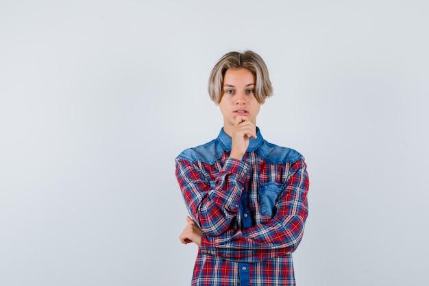 Ritratto di giovane ragazzo adolescente che tiene la mano sul mento in camicia a quadri e sembra una vista frontale sensata