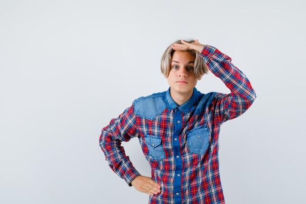 Ritratto di giovane ragazzo adolescente che tiene la mano sopra la testa in camicia a quadri e sembra curioso vista frontale