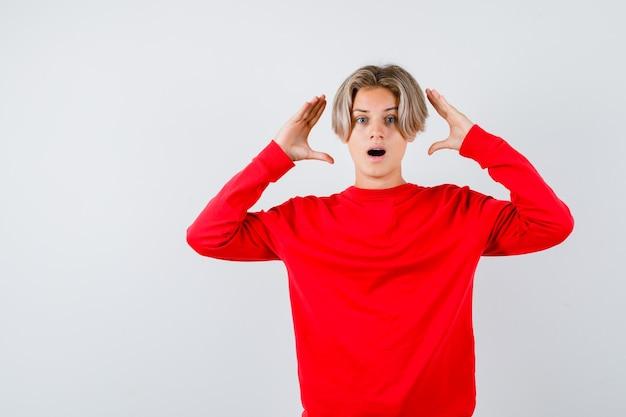 Ritratto di un giovane ragazzo adolescente che tiene le mani vicino alla testa con un maglione rosso e sembra una vista frontale ansiosa