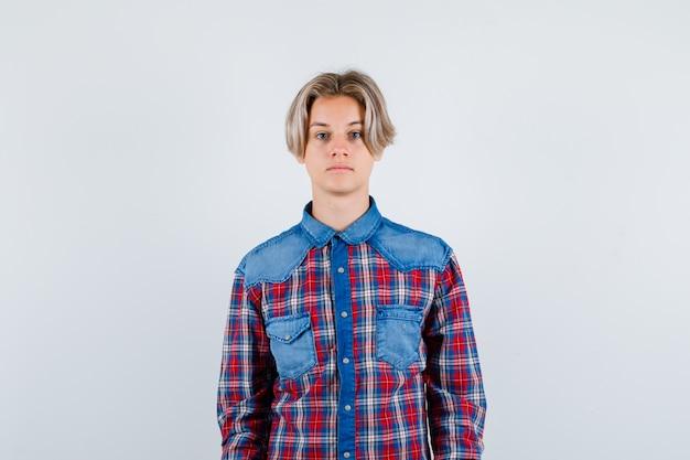 Ritratto di un giovane ragazzo adolescente che guarda la telecamera con una camicia a quadri e sembra una vista frontale intelligente