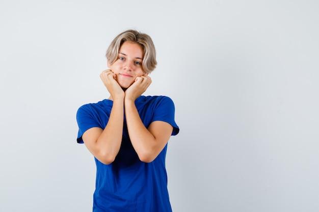Ritratto di giovane ragazzo adolescente che si fa il cuscino sulle mani con una maglietta blu e sembra una vista frontale positiva