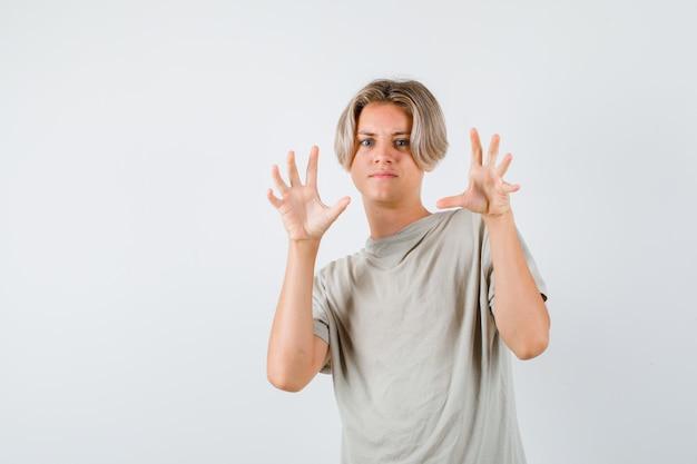 Ritratto di giovane ragazzo adolescente che mostra artigli che imitano un gatto in maglietta e che sembrano agili vista frontale