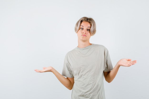 Ritratto di un giovane ragazzo adolescente che mostra un gesto impotente in maglietta e sembra una vista frontale indecisa