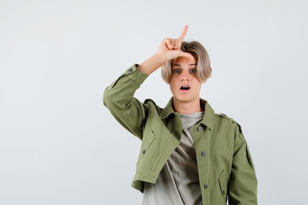 Ritratto di giovane ragazzo adolescente che mostra il segno del perdente sulla fronte in maglietta, giacca e sembra deluso vista frontale