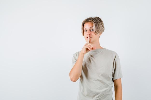 Ritratto di giovane ragazzo adolescente che mostra gesto di silenzio in maglietta e sembra una vista frontale sensata