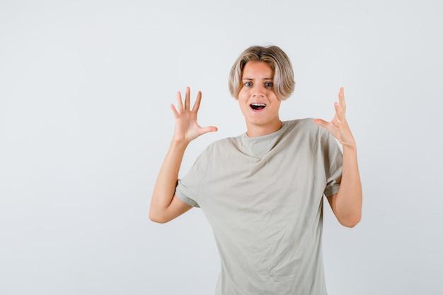 Ritratto di giovane ragazzo adolescente che mostra gesto di resa in maglietta e sembra terrorizzato vista frontale