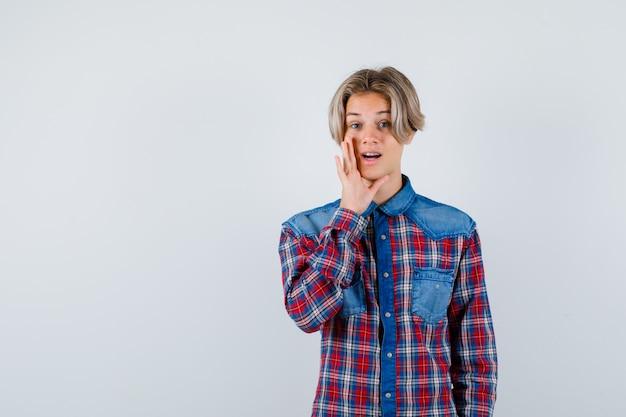 Ritratto di giovane ragazzo adolescente che dice il segreto dietro la mano in camicia a quadri e sembra curioso vista frontale