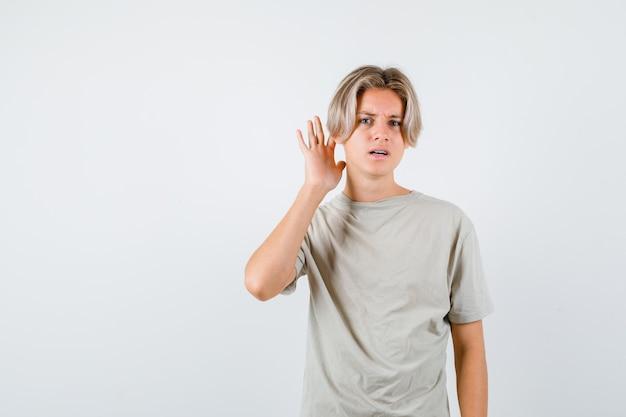 Ritratto di giovane ragazzo adolescente con la mano dietro l'orecchio in maglietta e guardando perplesso vista frontale