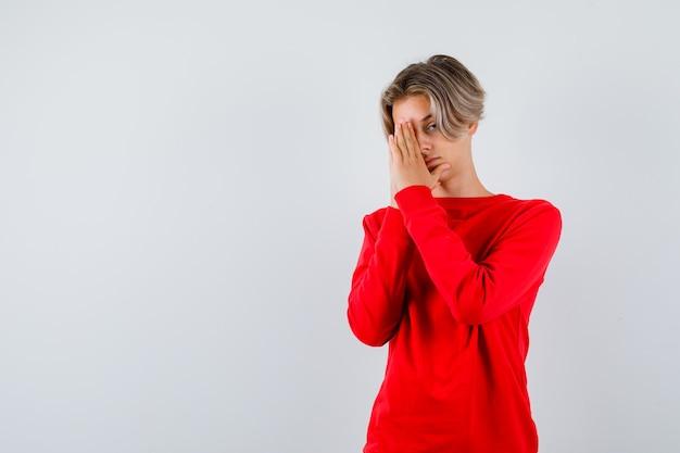 Ritratto di giovane ragazzo adolescente con le mani in gesto di preghiera in maglione rosso e guardando speranzoso vista frontale