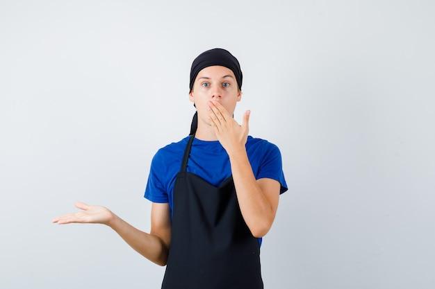Ritratto di giovane cuoco adolescente con la mano sulla bocca, allargando il palmo in maglietta, grembiule e guardando sorpreso vista frontale