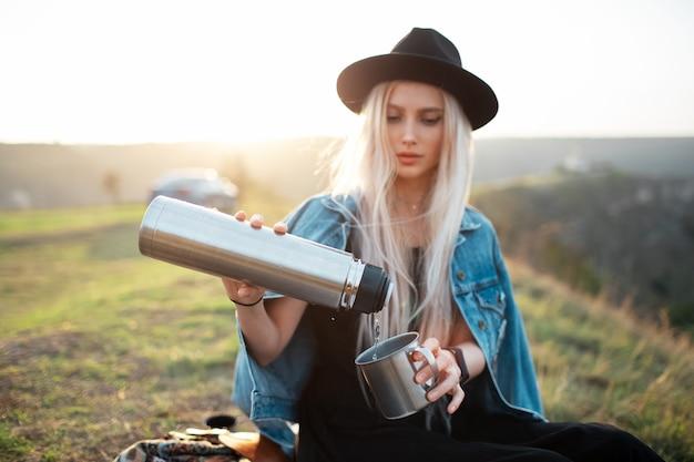 Ritratto di giovane ragazza bionda adolescente, versando il tè nella tazza d'acciaio dalla bottiglia del thermos.