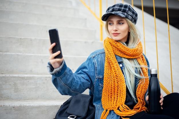 Ritratto di giovane adolescente ragazza bionda, prendendo selfie foto con lo smartphone