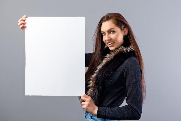 Ritratto di giovane donna adolescente che mostra cartello bianco con copia spazio, isolato su grigio