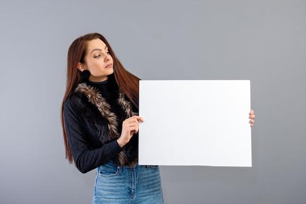 Ritratto di giovane donna adolescente che mostra cartello bianco con spazio copia, isolato su gray
