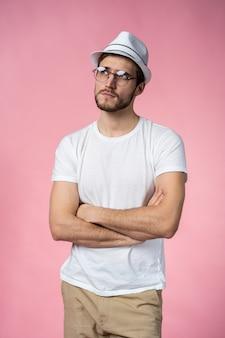 Il ritratto del giovane uomo di pensiero osserva in su - isolato sul colore rosa.