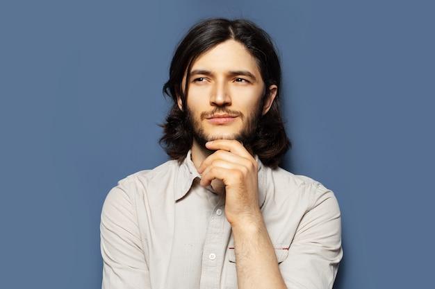 Ritratto di giovane uomo premuroso con i capelli lunghi che guardano lontano. sfondo di colore blu.