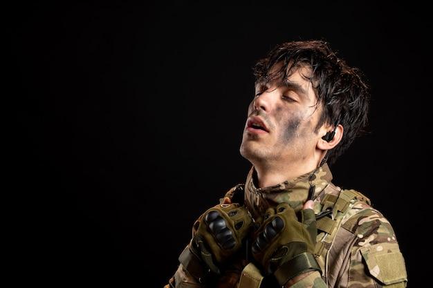 Ritratto di giovane soldato stanco in uniforme sul muro scuro
