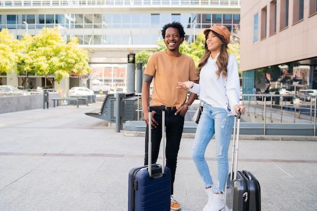 Ritratto di giovane coppia di turisti che trasportano la valigia stando in piedi fuori dall'aeroporto o dalla stazione ferroviaria. concetto di turismo.