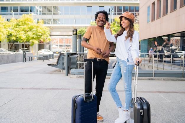 Ritratto di giovane coppia di turisti che trasportano la valigia stando in piedi fuori dall'aeroporto o dalla stazione ferroviaria